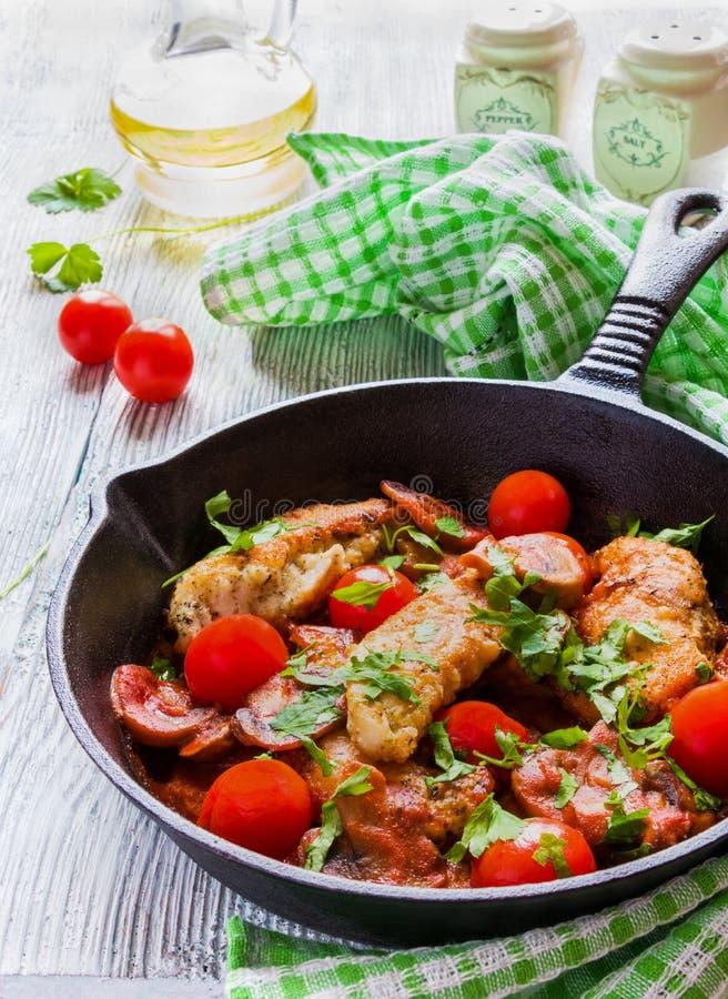 Grillad feg filé som lagas mat med champinjoner, vitlök, paprika och olivolja Järn- kastrull och nya körsbärsröda tomater royaltyfria foton