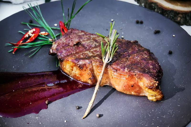 Grillad filé av nötkött som överträffas med röd sås för tomat på plattan royaltyfria foton