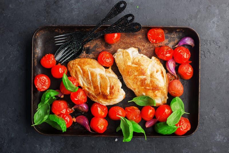 Grillad filé för fegt bröst med ung vitlök, körsbärsröda tomater på en bakplåt med basilikasidor Utrustad maträtt på a arkivfoto