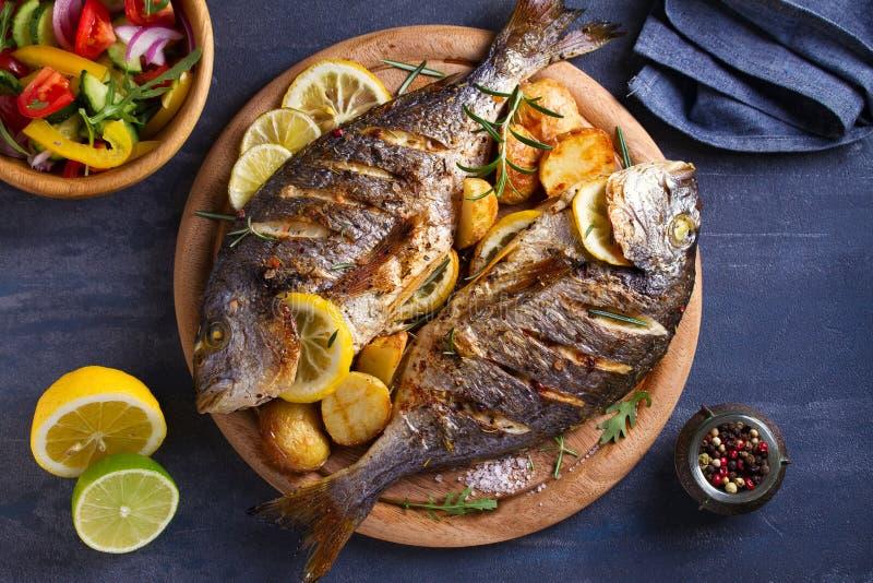 Grillad fisk med den grillade potatisar, citronen och rosmarin p? tr?magasinet royaltyfria foton