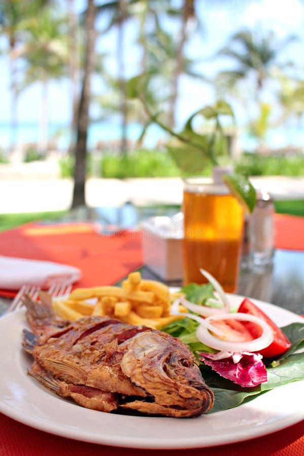 Grillad fisk med grönsaker som tjänas som i strandrestaurang arkivbild