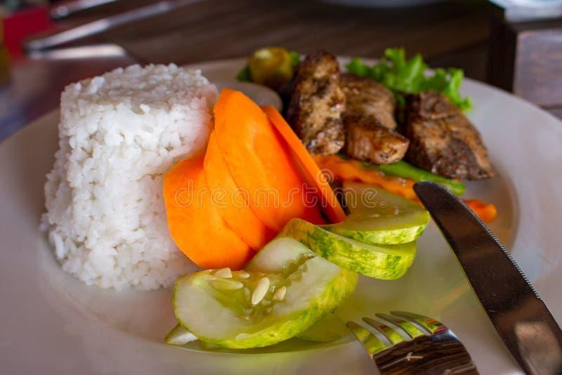 Grillad fisk med vita ris och nya grönsaker och gaffel med kniven Asiatiskt kokkonstbegrepp royaltyfri foto