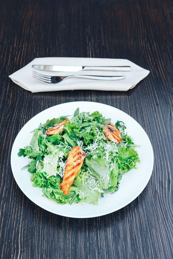 Grillad fisk och ny grön sallad på en vit platta spelrum med lampa royaltyfria foton