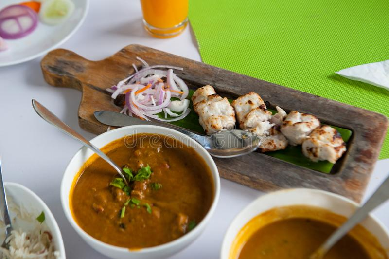 Grillad fisk på träplattan med currysås royaltyfri foto