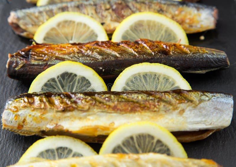 Grillad fisksaury med citronen på ett kritiserabräde royaltyfri bild