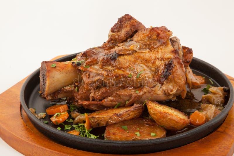 Grillad grisköttbenknoge med grönsaker fotografering för bildbyråer