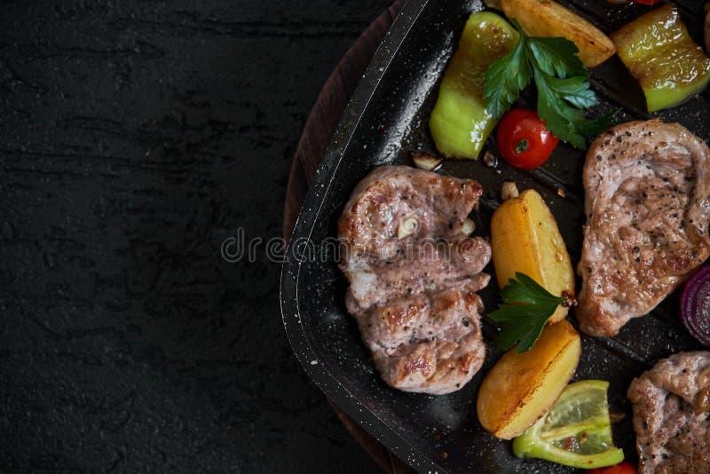 Grillad grisköttbifffilé i stekpanna över mörk bakgrund, bästa sikt arkivfoto