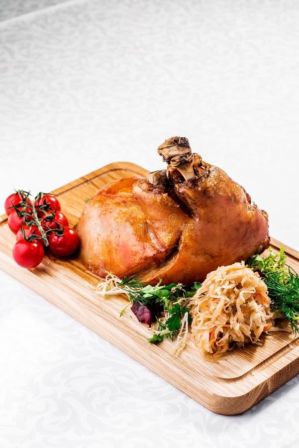 Grillad grisköttknoge med bräserade kokta kål och tomater på träskärbräda royaltyfri fotografi