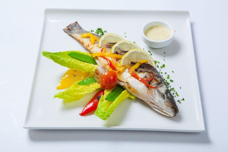 Grillad hel fisk som dekoreras med sidor av grönsallat och den körsbärsröda tomaten som tjänas som med vitlöksås fisk stekt helt arkivfoto
