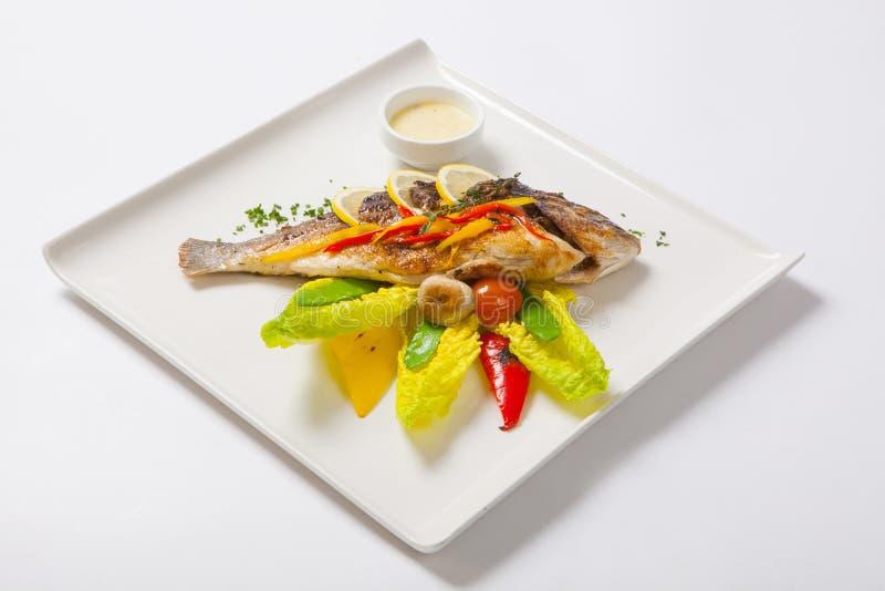 Grillad hel fisk som dekoreras med sidor av grönsallat och den körsbärsröda tomaten som tjänas som med vitlöksås fisk stekt helt royaltyfri fotografi