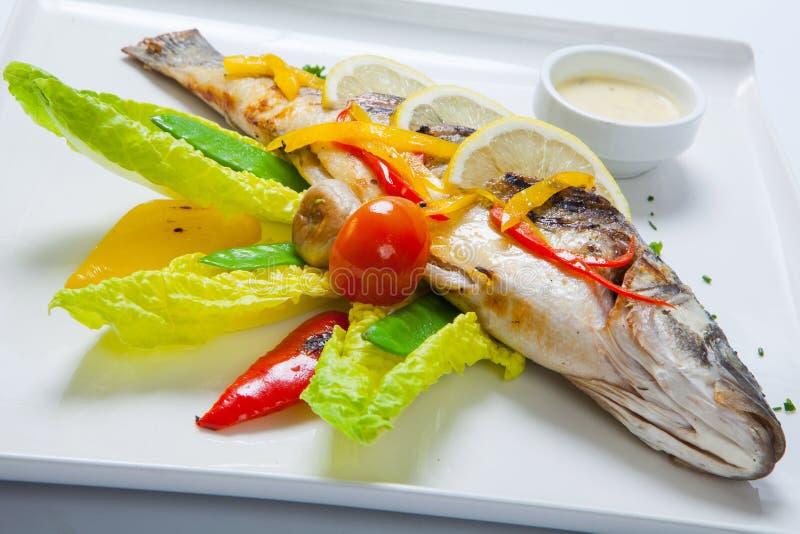Grillad hel fisk som dekoreras med sidor av grönsallat och den körsbärsröda tomaten som tjänas som med vitlöksås fisk stekt helt arkivbilder