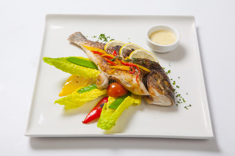 Grillad hel fisk som dekoreras med sidor av grönsallat och den körsbärsröda tomaten som tjänas som med vitlöksås fisk stekt helt royaltyfria foton