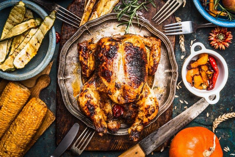 Grillad hel kalkon eller höna med organisk skördgrönsaker och pumpa för tacksägelsematställe på lantlig tabellbakgrund royaltyfri foto