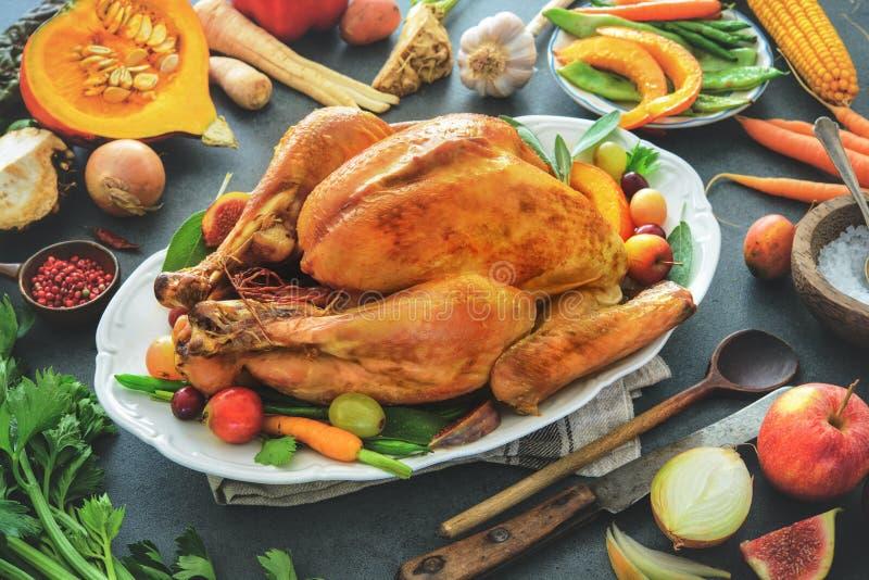 Grillad hel kalkon med matlagningingredienser på köksbordet royaltyfri fotografi