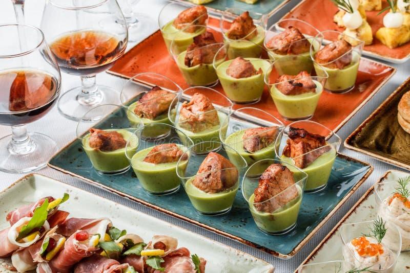 Grillad köttfilé med grön mousse i exponeringsglaskoppar på banketttabellen Sk?ta om mat, canape och mellanm?l fotografering för bildbyråer