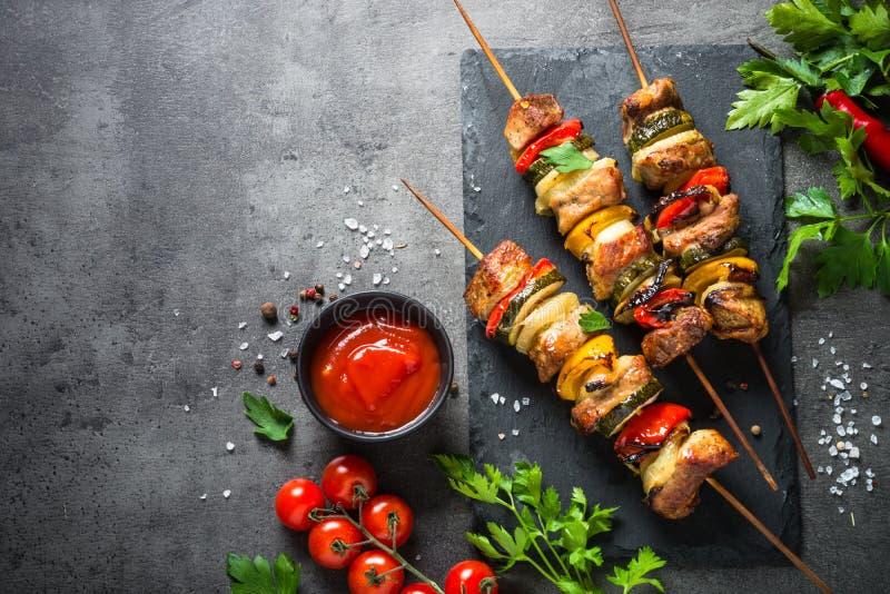 Grillad kebab med grönsaker på svart royaltyfri fotografi