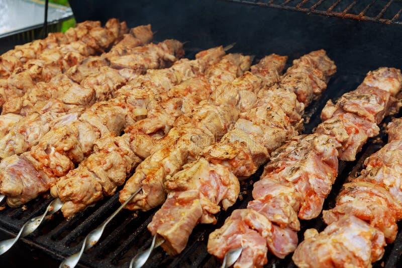 Grillad kebab på metallsteknålen Kocken räcker den matlagning grillade köttgrillfesten med massor av rök arkivfoto