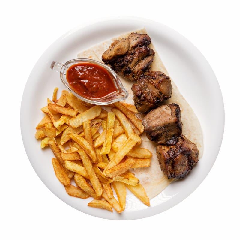 Grillad kebab som tjänas som med franska småfiskar och sås som isoleras på vit bakgrund royaltyfri bild