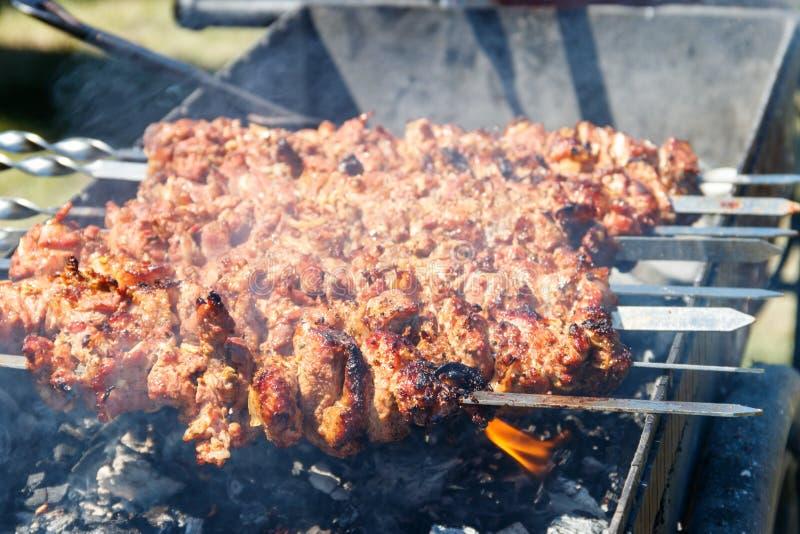 Grillad kebabmatlagning p? metallstekn?len Grillat k?tt som lagas mat p? grillfesten royaltyfri bild