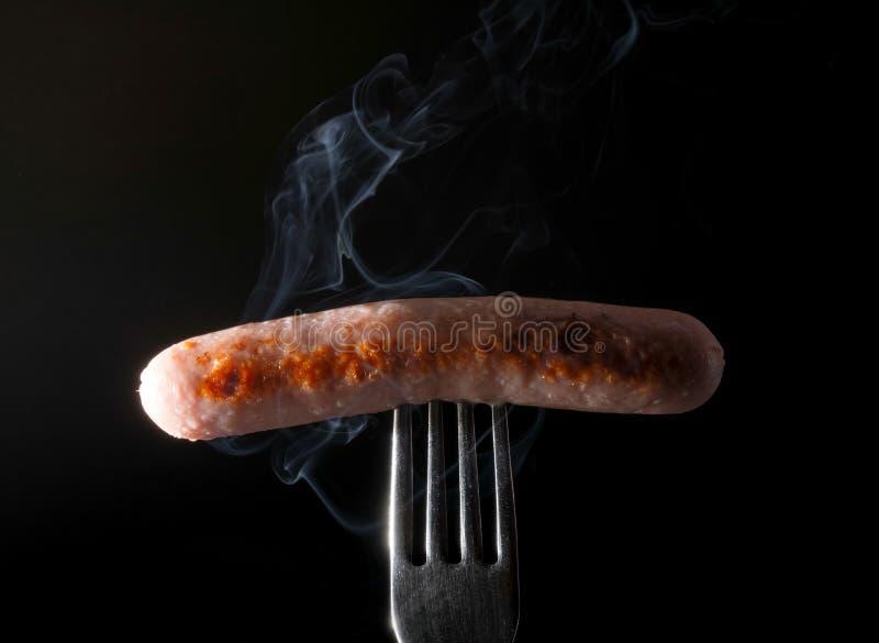 Grillad korv på en gaffel som ångar bakgrund för röksvart royaltyfria bilder