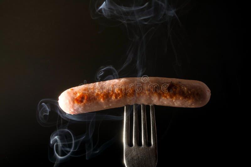 Grillad korv på en gaffel som ångar bakgrund för röksvart royaltyfri bild