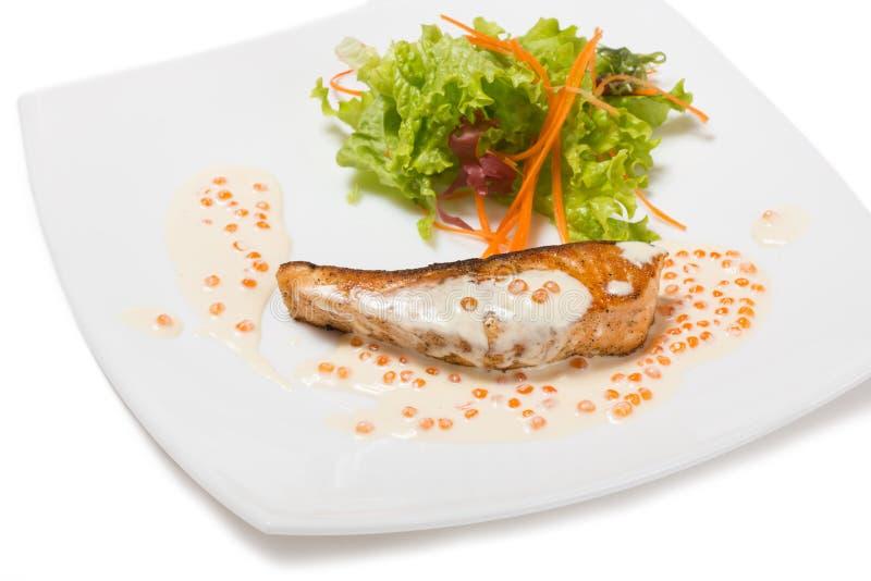 Grillad lax i en krämig kaviarsås. royaltyfri fotografi
