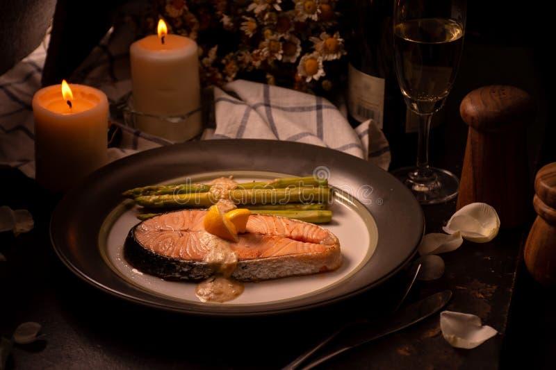 Grillad lax och sparris på plattan med exponeringsglas av vitt vin royaltyfri foto