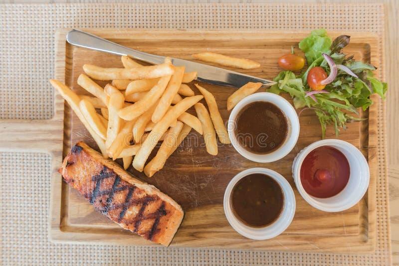Grillad laxbiff med sallad- och fransmansmåfiskar arkivbild