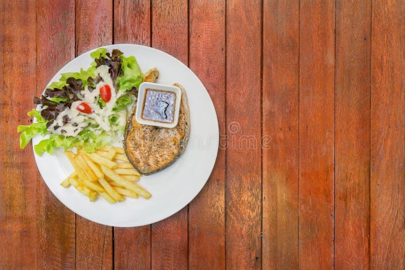 Grillad laxbiff, serve med fransmansmåfiskar och salladvegetabl royaltyfri bild