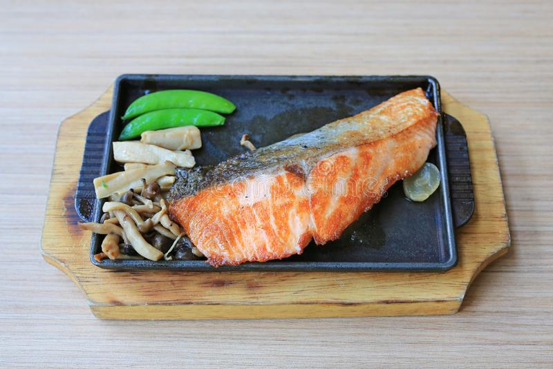 Grillad laxbiff tjänade som med grönsaker på den varma plattan Japansk kokkonstmat royaltyfri bild