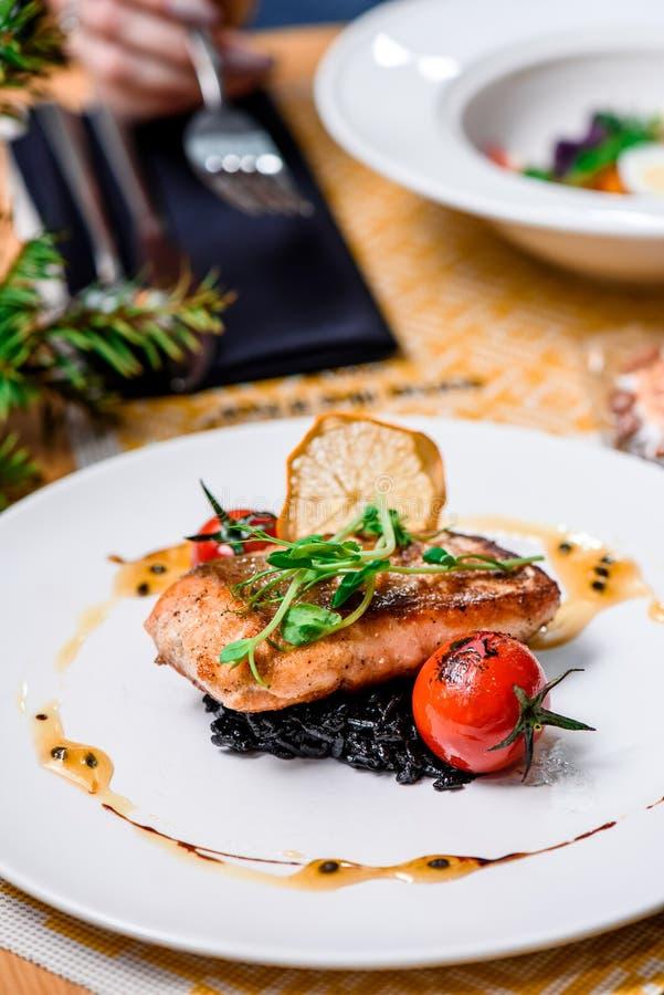 Grillad laxfilé och risotto med bläckfiskfärgpulver på en vit platta i en restaurang close upp royaltyfria bilder