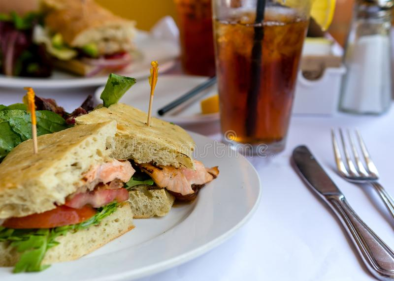 Grillad laxsmörgås i ciabattabröd i restaurangen royaltyfria bilder