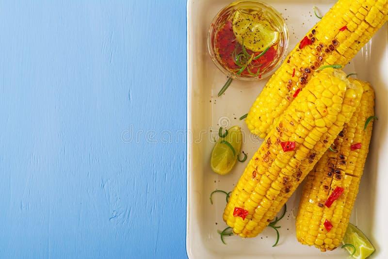 Grillad majs med mexikansk sås, chili och limefrukt på blå bakgrund royaltyfria bilder