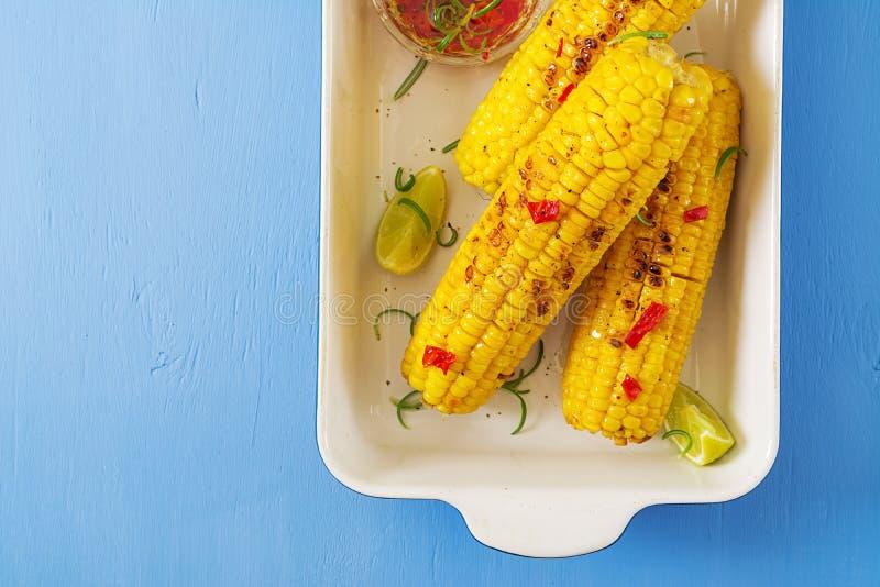 Grillad majs med mexikansk sås, chili och limefrukt på blå bakgrund arkivfoton
