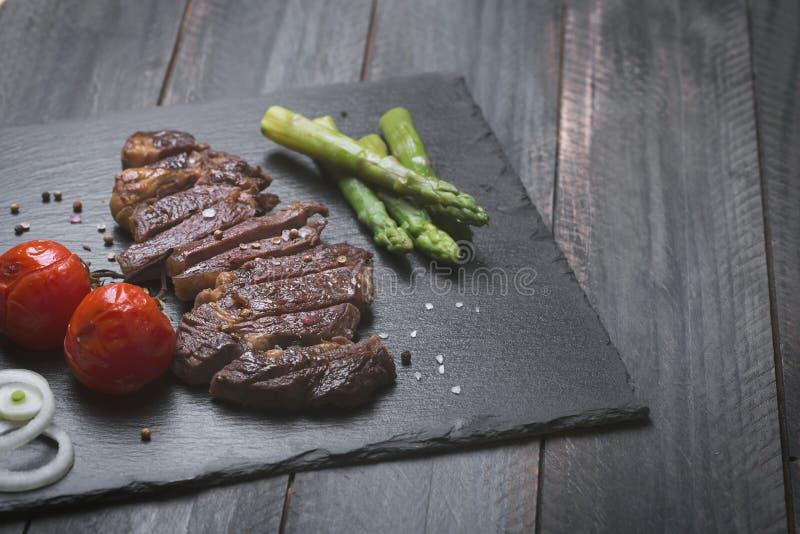 Grillad nötköttbiff med grönsaker på en svart bakgrund royaltyfri foto