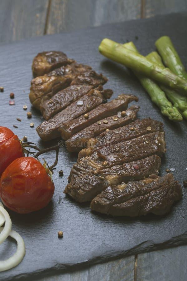 Grillad nötköttbiff med grönsaker på en svart bakgrund arkivfoton