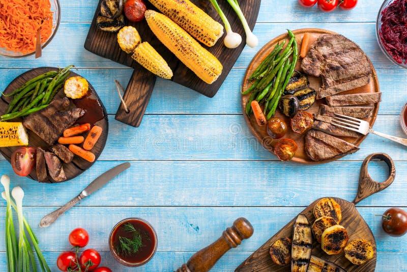 Grillad nötköttbiff med grillade grönsaker på träblåtttabellen royaltyfria bilder