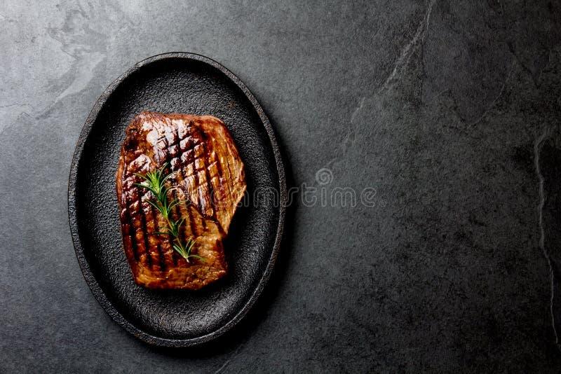 Grillad nötköttbiff på den svarta gjutjärnplattan Bakgrund med kopieringsutrymme Grillfest fläskkarré för bbq-köttnötkött Top bes royaltyfri bild