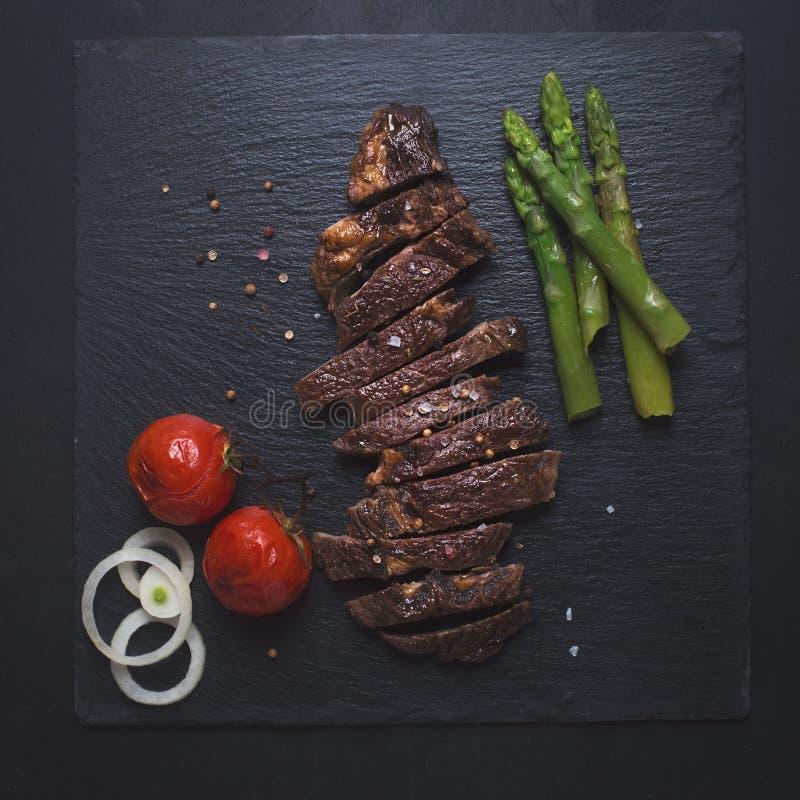 Grillad nötköttbiff på en svart bakgrund royaltyfri foto