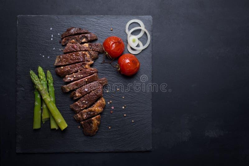 Grillad nötköttbiff på en svart bakgrund med kopieringsutrymme arkivfoton