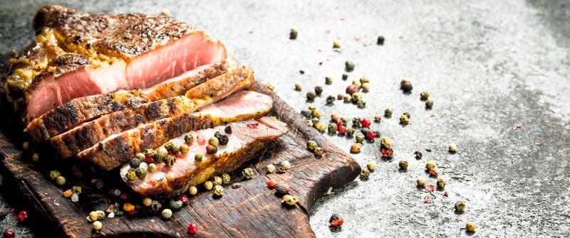 Grillad nötköttbiff på en svart tavla med kryddor fotografering för bildbyråer