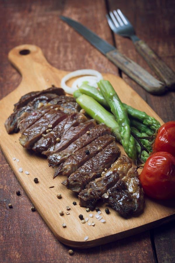Grillad nötköttbiff på en trälantlig bakgrund fotografering för bildbyråer