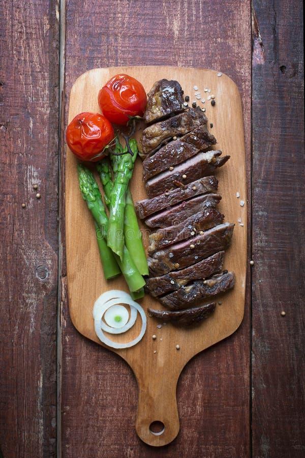 Grillad nötköttbiff på en trälantlig bakgrund för ljus skärbräda arkivfoton