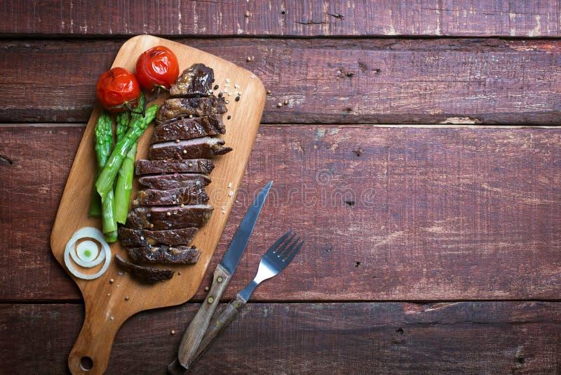 Grillad nötköttbiff på ett matlagningbräde och en trälantlig bakgrund arkivfoton