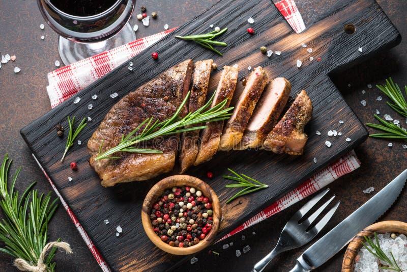 Grillad nötköttstriploinbiff med rött vinexponeringsglas royaltyfria bilder