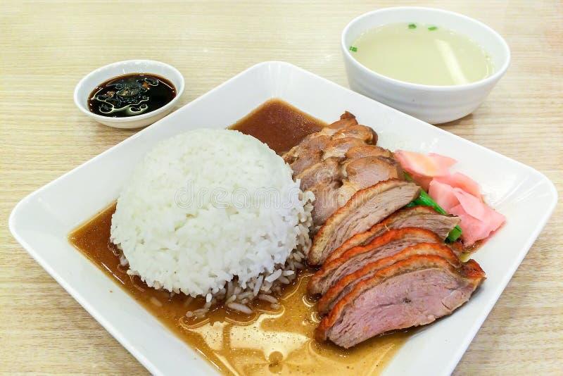 Grillad and och rött griskött med ris på plattan för vit fyrkant som tjänas som med sås och soppa på trätabellen arkivbild