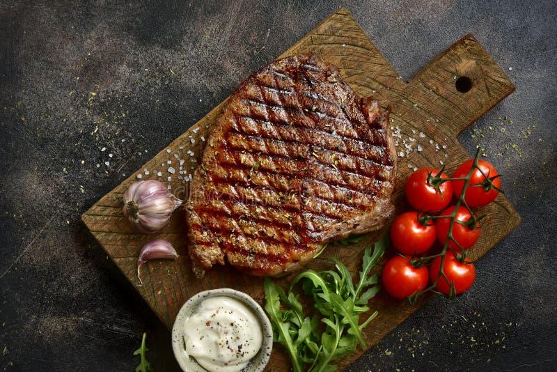Grillad organisk ranchonötköttbiff med grönsaker och vitlöksås på en träskärbräda Bästa sikt med kopieringsutrymme fotografering för bildbyråer