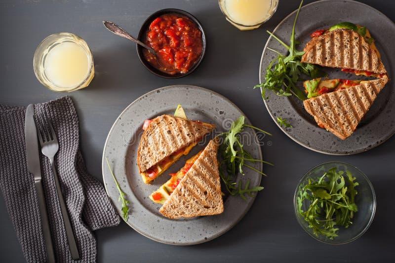 Grillad ostsmörgås med avokadot och tomaten arkivbild