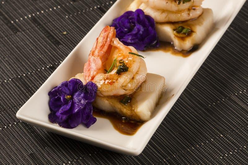 Grillad räka med rått spikar fisken på den vita plattan på tabellen royaltyfria foton
