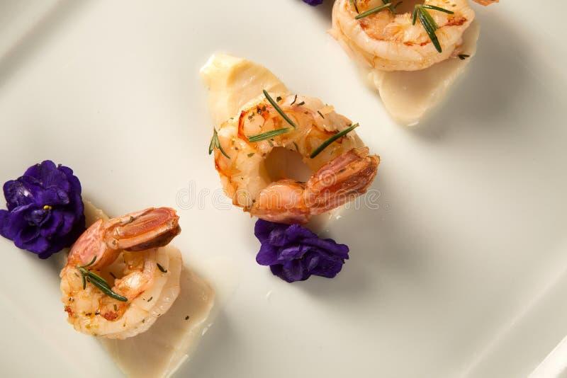 Grillad räka med rått spikar fisken på den vita plattan på tabellen royaltyfria bilder